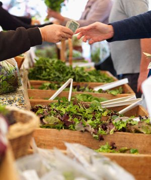 People buying lettuce at farmers market