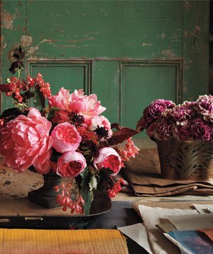 2 bouquets of lush pink and purple flowers on table with rustic, earth-toned background