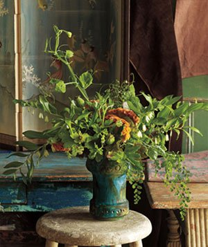 A mostly green bouquet of flowers and leaves in a painted ceramic vase