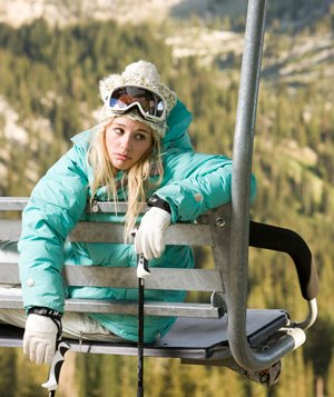 Skier on a chairlift looking unhappy
