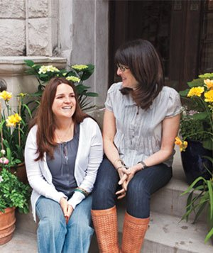 2 Women sitting on outdoor staircase surrounded by potted flowers