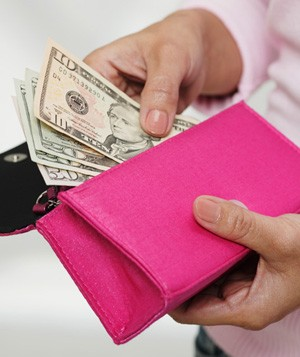 Woman taking money out of wallet