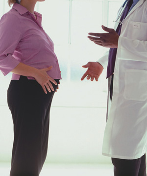 Pregnant woman standing with a male doctor