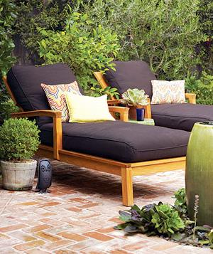 Brick patio with two wooden lounge chairs with brown fabric cushions