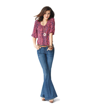 Model wearing pink printed blouse, flared jeans, wooden bracelets and heels