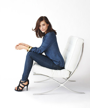 Model sitting in white chair wearing dark denim outfit and high heeled sandals