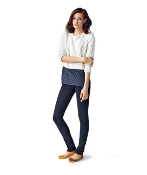 Model wearing white sweater, polka-dot top, skinny jeans and flats