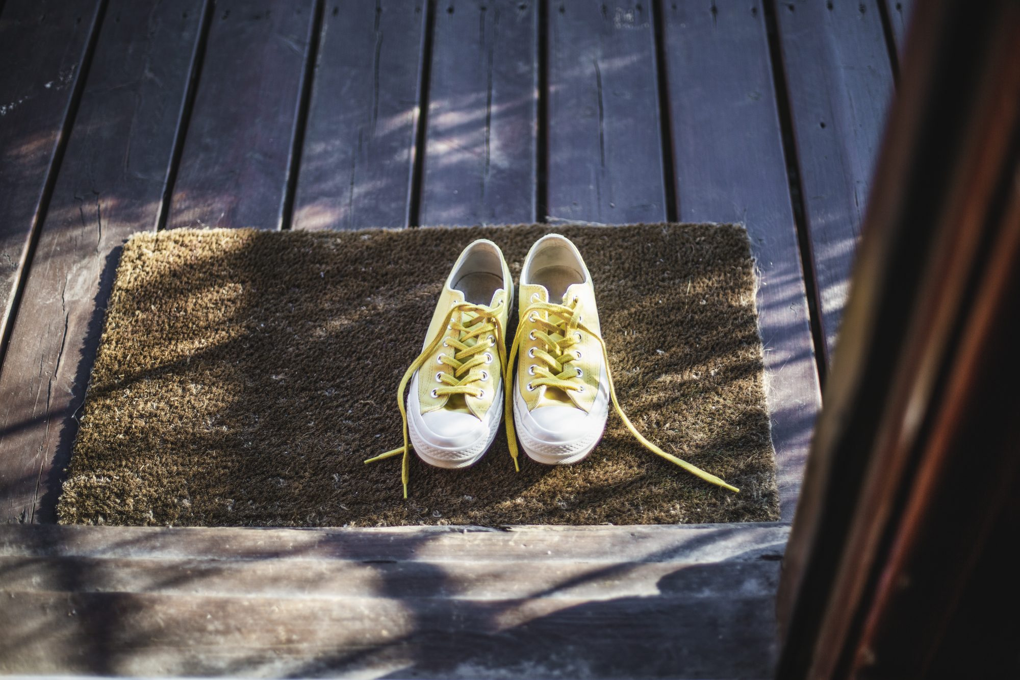 yellow sneakers on the door mat outside