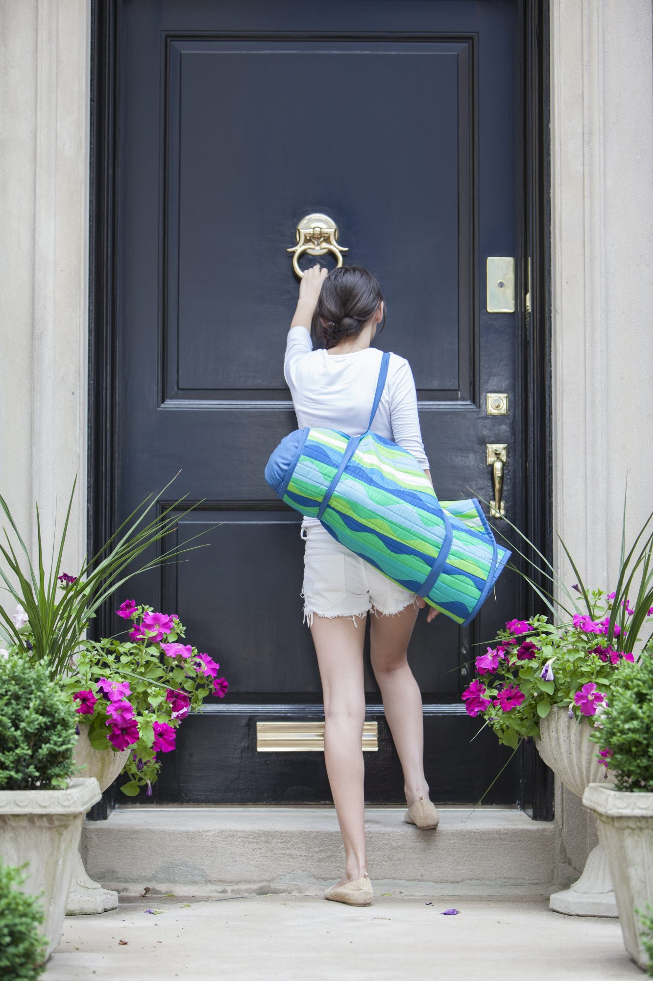Woman with luggage knocking on a door