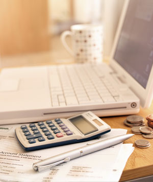 Laptop, calculator, pen, and coins on a desk