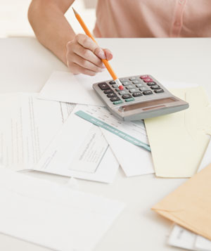 Woman reviewing her finances with a calculator