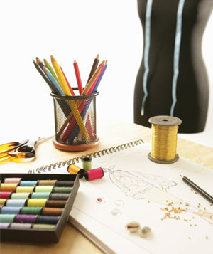 Pencils, thread, dressform, and other tools in a fashion designer's studio