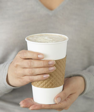 Woman holding a cup of coffee in a cardboard sleeve