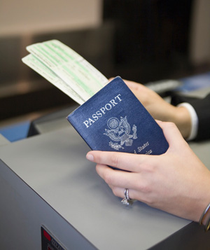 Passport and boarding passes in woman's hands at check-in counter