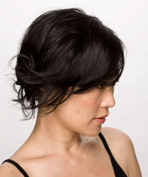 Smiling model with black hair in a simple side knot