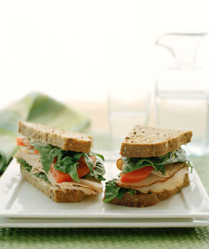 Turkey sandwich on white plate with water in back