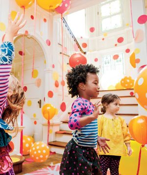 Little girls at a party playing with a room full of orange and yellow balloons