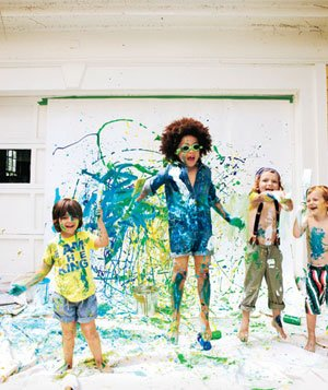 4 little boys covered in paint, jumping and splashing paint around