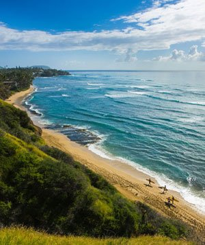 Long sandy beach with surfers walking at distance