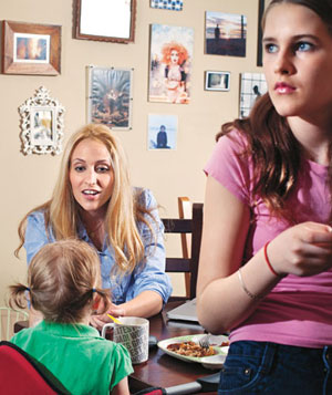 Mother feeds baby, teenager in foreground with cell phone