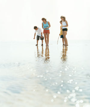 Mom on the beach with her children