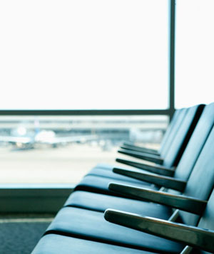 Row of empty seats by window in airport terminal waiting area