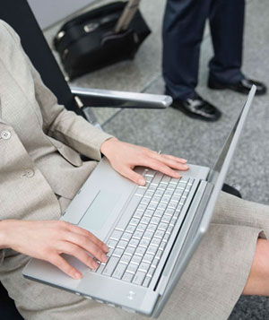 Hands of businesswoman using laptop computer at airport