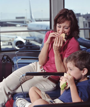 Mother and son eating sandwiches in airport waiting area