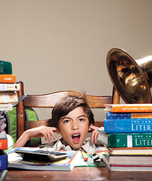 Boy sits at large desk with textbooks, plugging ears