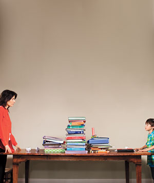 Mother and child standing across from each other at large table covered with books