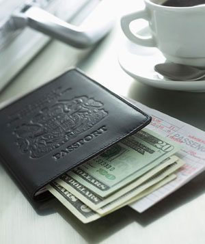 Passport, US cash, airplane ticket on a table