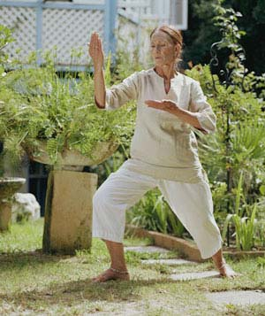 Senior woman in garden practising Tai Chi