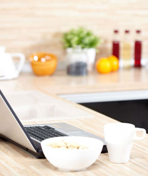Laptop on kitchen counter with coffee mug and cereal