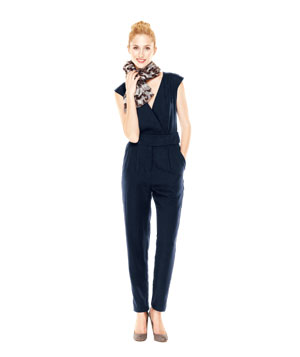 Model wearing balck sleeveless jumpsuit, patterned scarf and brown heels