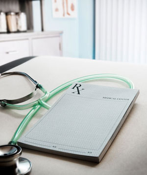 Stethoscope and notepad on desk in doctor's office