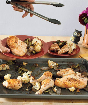 Man serving roasted chicken and cauliflower from roasting pan