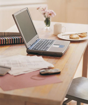 Laptop, cell phone, papers and breakfast on kitchen table