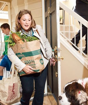 Mother  carrying groceries entering through front door into busy home