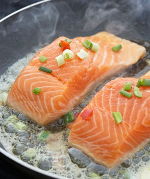 Salmon fillets cooking in a pan on the stove