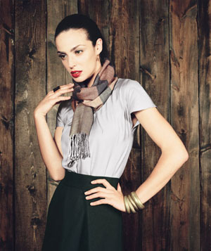 Model wearing grey silk blouse, black skirt, plaid scarf and chunky gold bangles