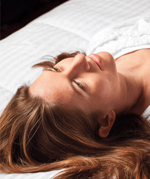 Close-up of a woman laying on her bed looking away from camera