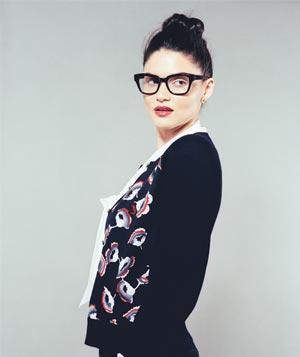 Model with black-rimmed glasses wearing black knit cardigan with flower print