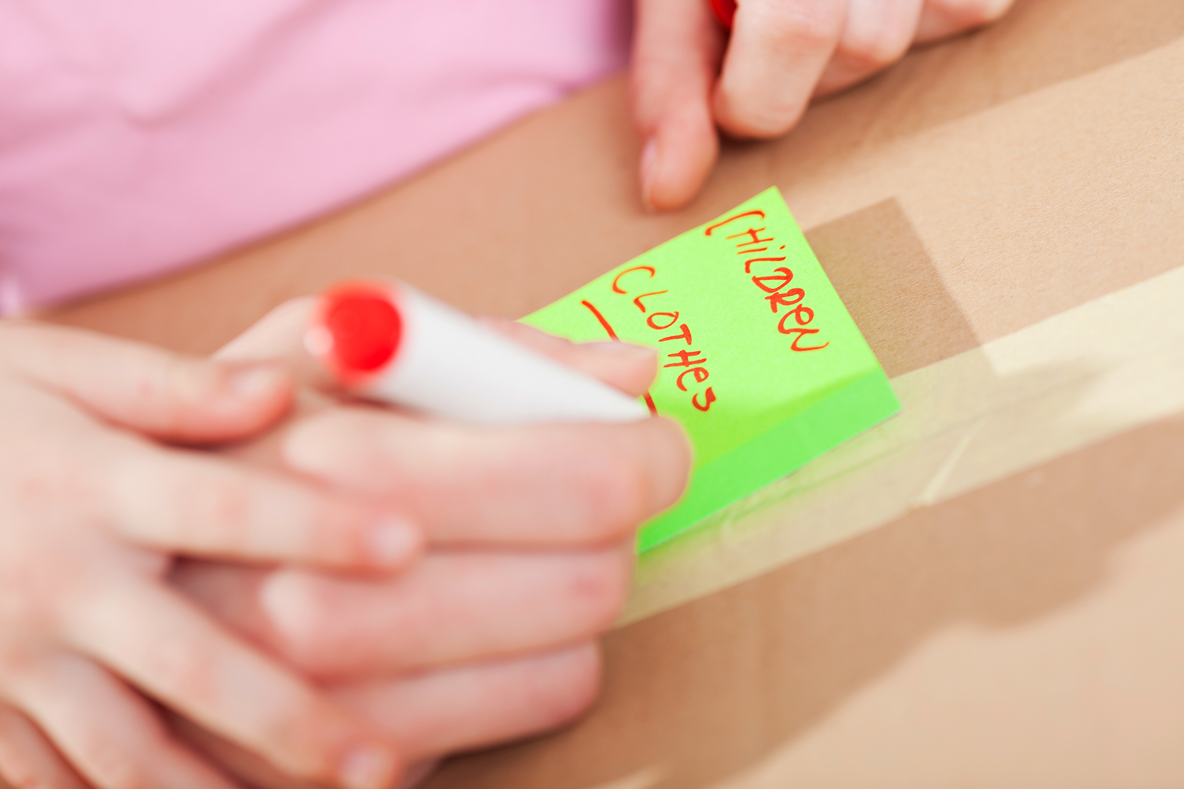 Woman labeling boxes decluttering solutions