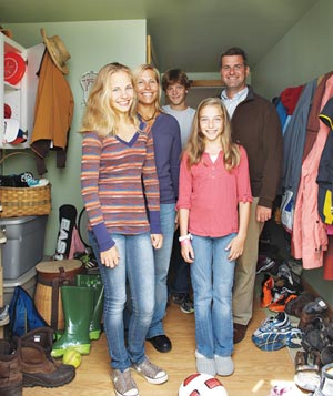 Smiling family in their messy mudroom