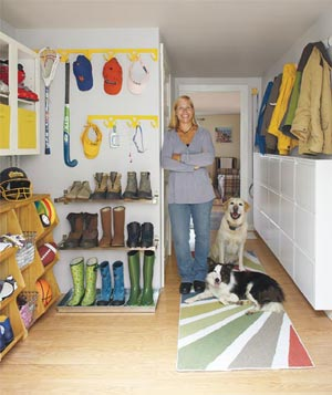 Woman smiling with her dog in her organized mudroom