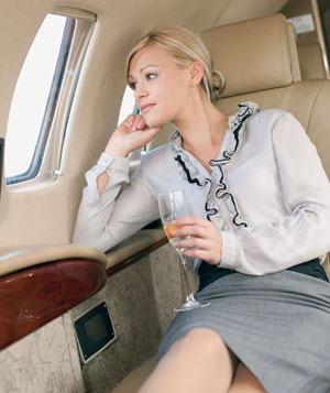 Woman drinking champagne in first class cabin of airplane