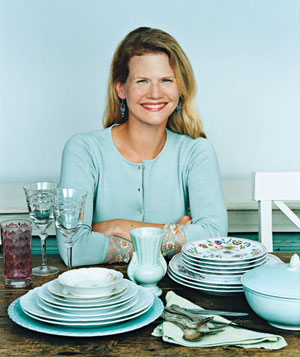 Woman sitting at table with stacks of china