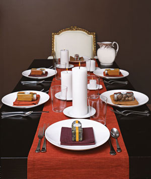 Dinner table setting with jars of spices in place of napkin rings