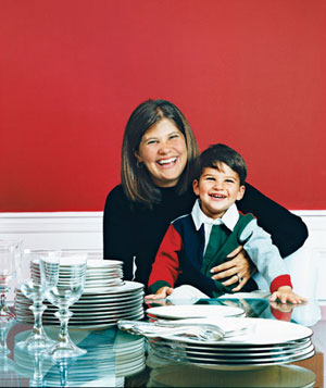 Woman and young son sitting at table with piles of flatware