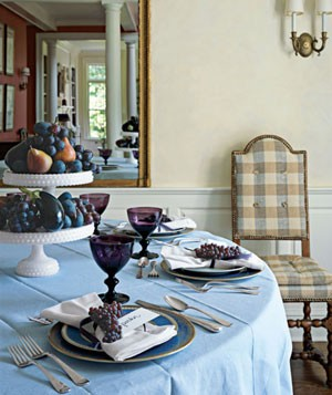 Romatic table decor featuring grape place cards, an edible centerpiece, and blue-and-gold china
